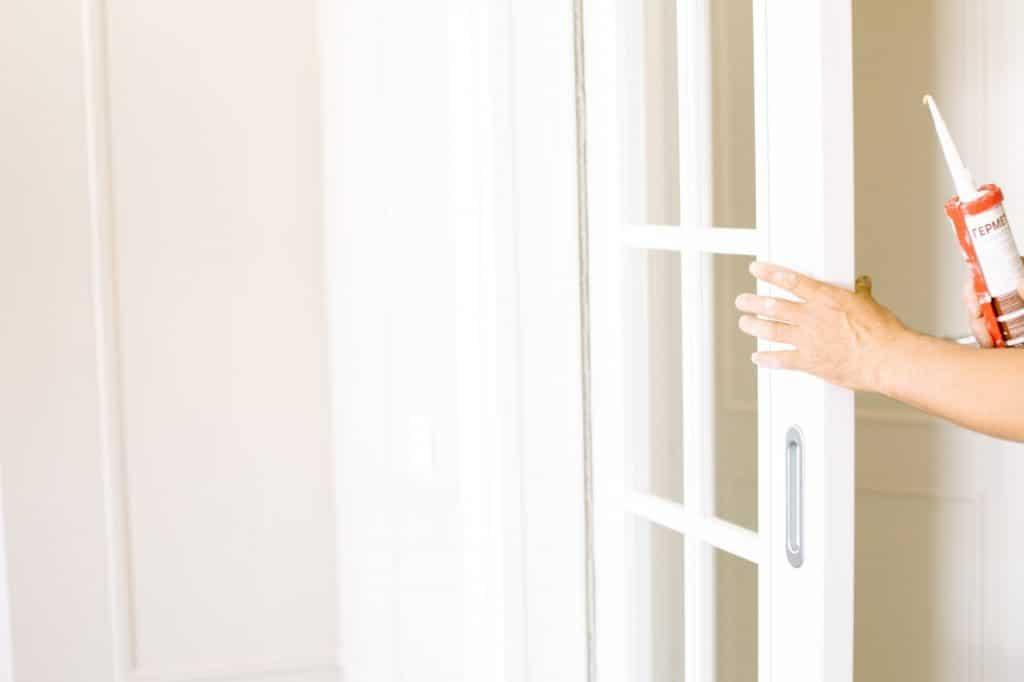 Homme fermant une fenêtre pour poser des plinthes en carrelage avec un pistolet à colle