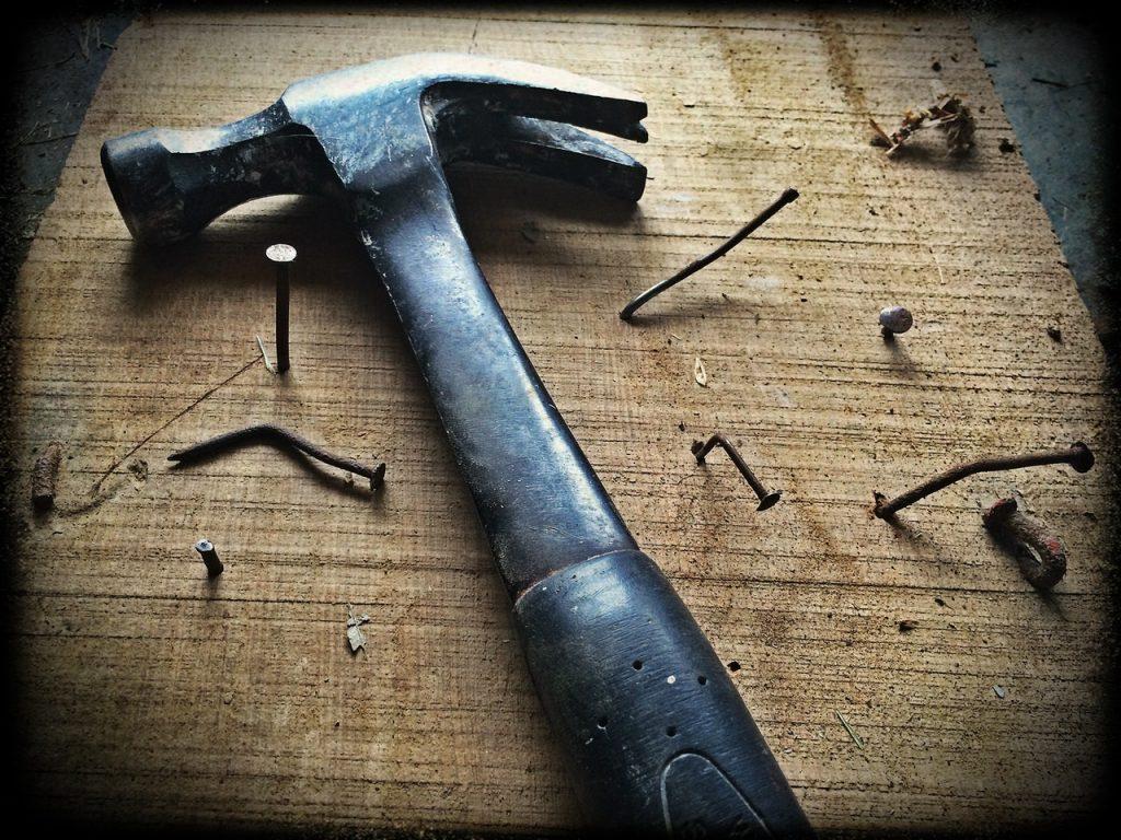 Planche de bois avec clous tordus et marteau