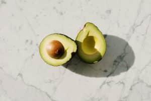 Avocat coupé en deux, posé sur une table en marbre