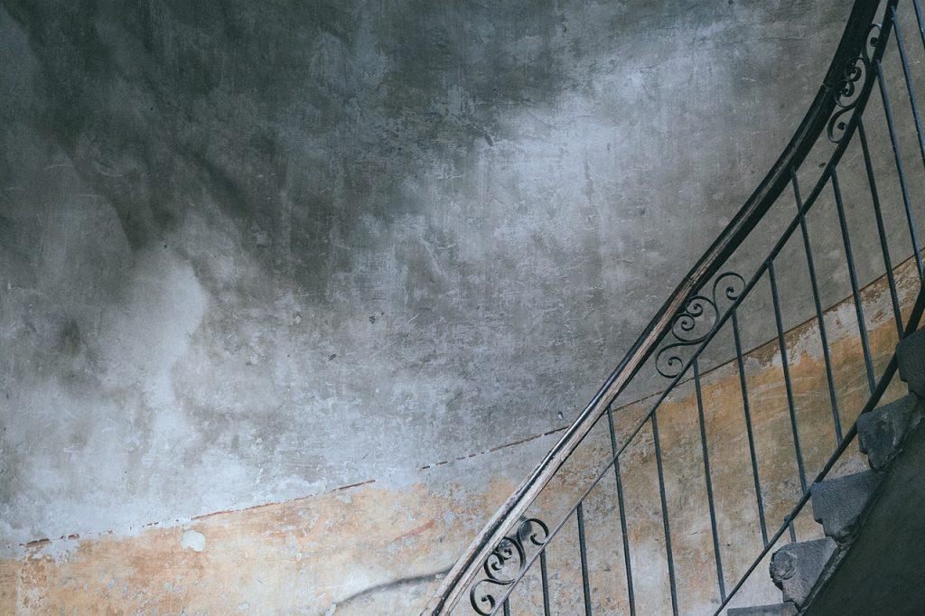 Escalier tournant lugubre, en colimasson, barreaux en fer forgé