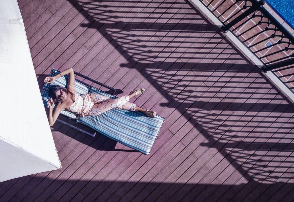 Femme sur chaise longue sur une terrasse au soleil