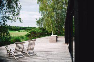Grande terrasse en bois avec plancher, chaise vue sur jardin