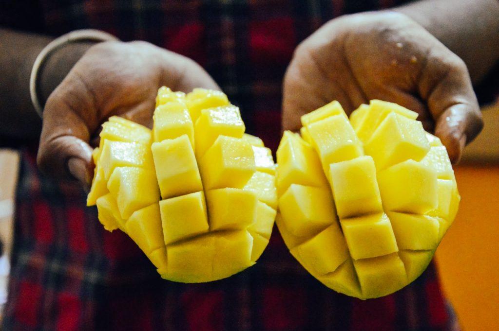 Mangue tenu en main, coupé en deux, morceaux