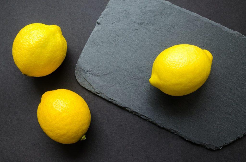 Trois citrons jaunes sur une planche en ardoise