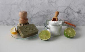 Petit bocal transparent avec bicarbonate de soude en poudre, citron vert coupé en deux et savon de marseilles