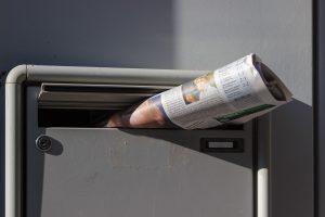 Boîte aux lettres avec journal dans la fente