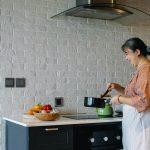 Femme heureuse cuisinant dans sa cuisine, utilisant sa hotte aspirante