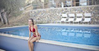 Femme assise au bord d'une piscine hors sol
